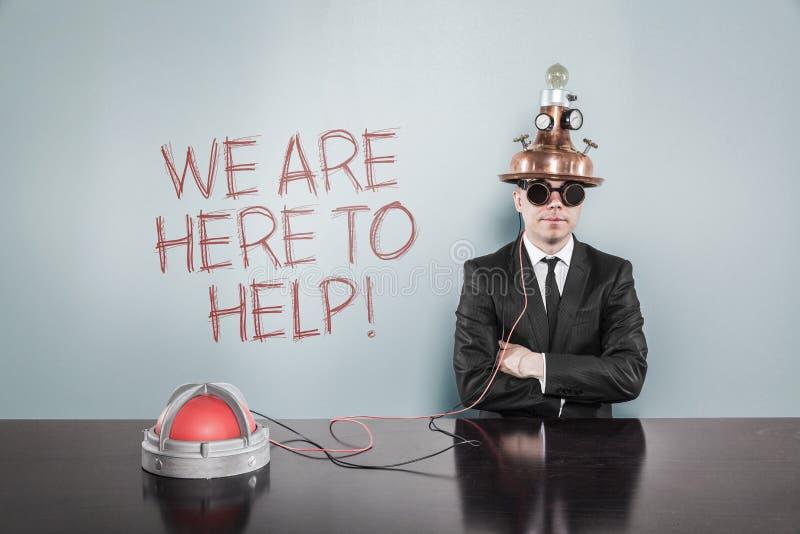 Επιχειρηματίας που φορά τη συνεδρίαση κρανών από το κείμενο στον γκρίζο τοίχο στοκ εικόνες
