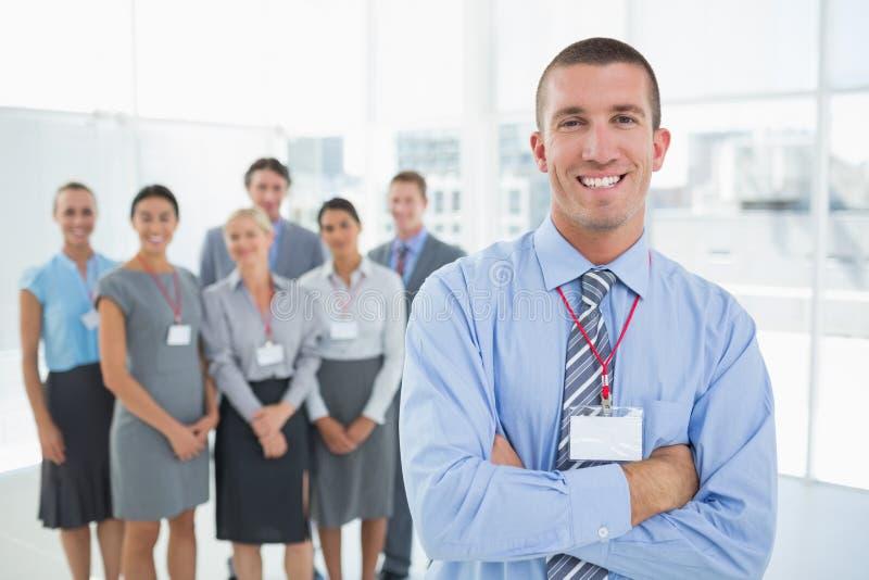 Επιχειρηματίας που χαμογελά στη κάμερα με την ομάδα πίσω από τον στοκ φωτογραφίες