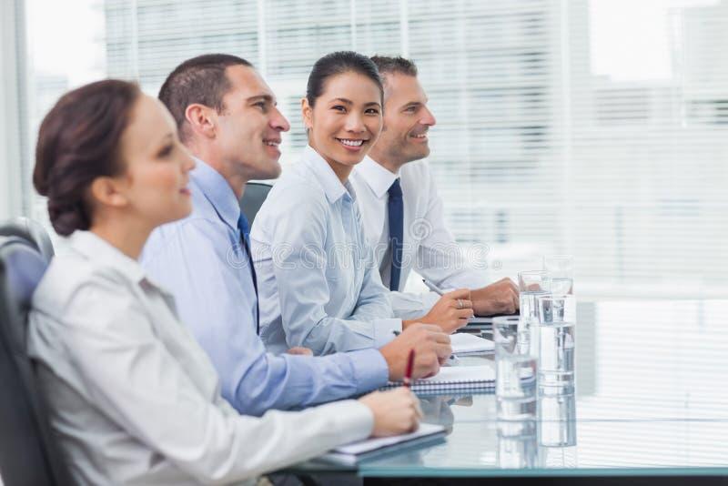 Επιχειρηματίας που χαμογελά στη κάμερα το άκουσμα συναδέλφων της στοκ φωτογραφία