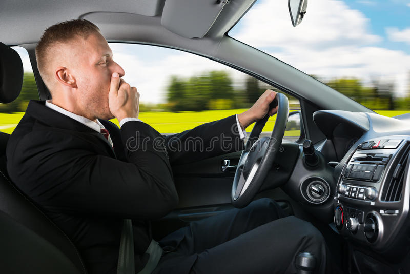 Επιχειρηματίας που χασμουριέται οδηγώντας το αυτοκίνητο στοκ φωτογραφίες