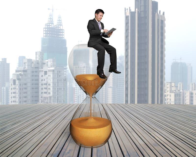 Επιχειρηματίας που χρησιμοποιεί την έξυπνη συνεδρίαση μαξιλαριών στο γυαλί ώρας στοκ φωτογραφία με δικαίωμα ελεύθερης χρήσης