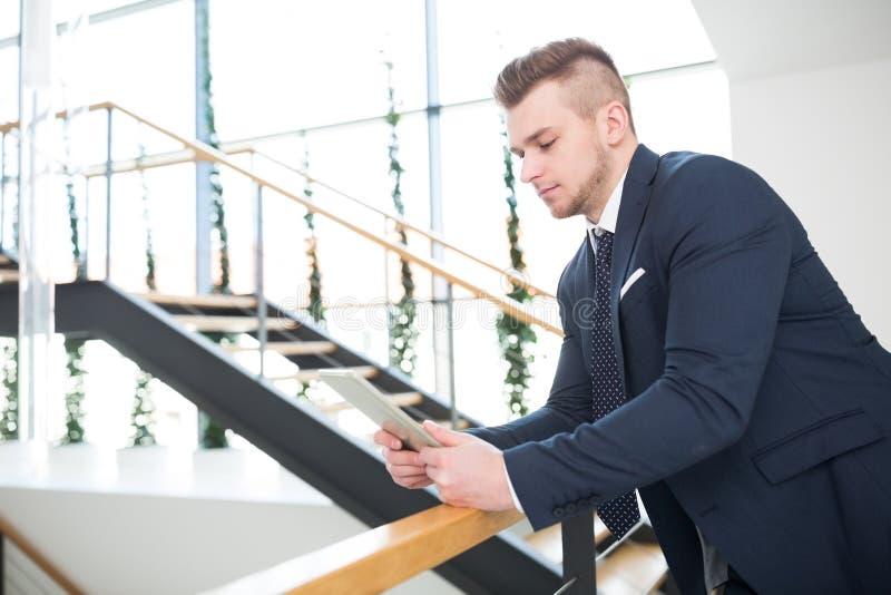 Επιχειρηματίας που χρησιμοποιεί την ψηφιακή ταμπλέτα κλίνοντας στο κιγκλίδωμα στοκ φωτογραφία με δικαίωμα ελεύθερης χρήσης