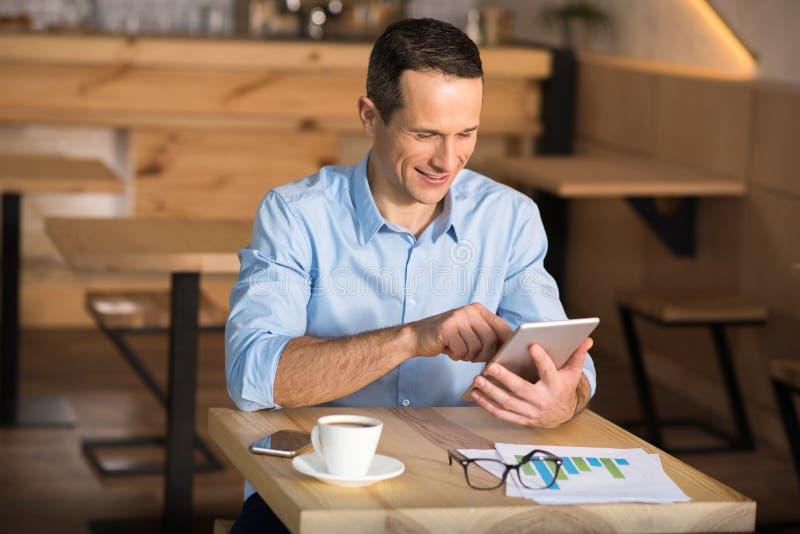 Επιχειρηματίας που χρησιμοποιεί την ψηφιακή ταμπλέτα στον καφέ στοκ φωτογραφία