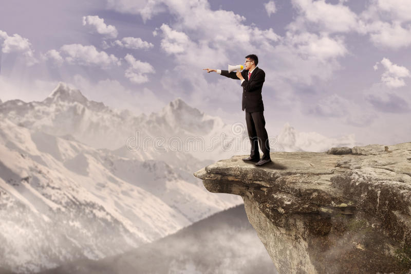 Επιχειρηματίας που χρησιμοποιεί τον ομιλητή στον απότομο βράχο στοκ φωτογραφία με δικαίωμα ελεύθερης χρήσης