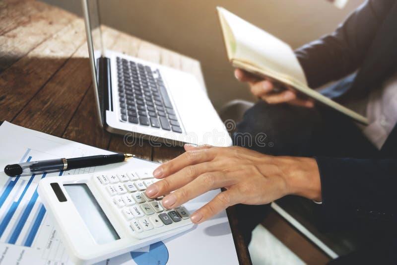 Επιχειρηματίας που χρησιμοποιεί τον υπολογιστή που αναλύει στα κέρδη επιχείρησης σε ένα σύγχρονο γραφείο στοκ εικόνα