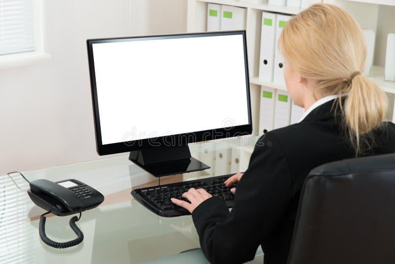 Επιχειρηματίας που χρησιμοποιεί τον υπολογιστή στο γραφείο στοκ εικόνες