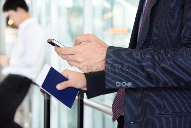Επιχειρηματίας που χρησιμοποιεί το έξυπνο τηλέφωνο κρατώντας το διαβατήριο σε άλλο στοκ εικόνες