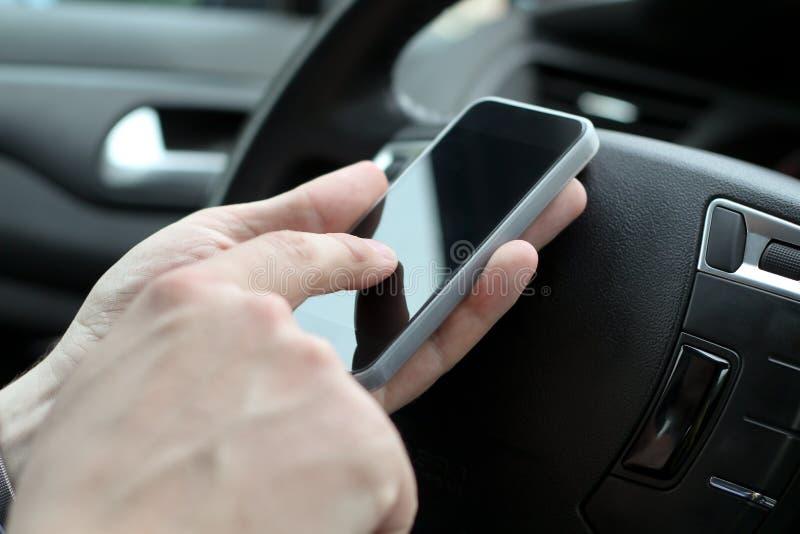 Επιχειρηματίας που χρησιμοποιεί το κινητό έξυπνο τηλέφωνο οδηγώντας το αυτοκίνητο στοκ εικόνα