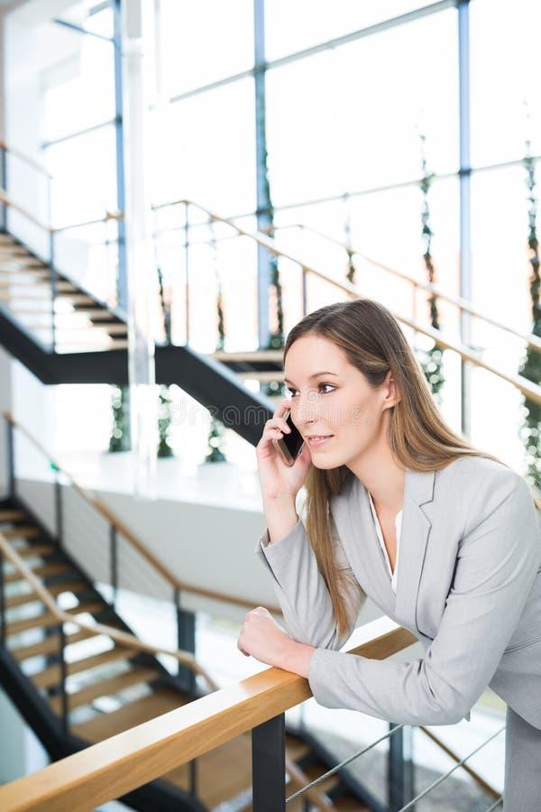 Επιχειρηματίας που χρησιμοποιεί το κινητό τηλέφωνο κλίνοντας στο κιγκλίδωμα στοκ φωτογραφίες