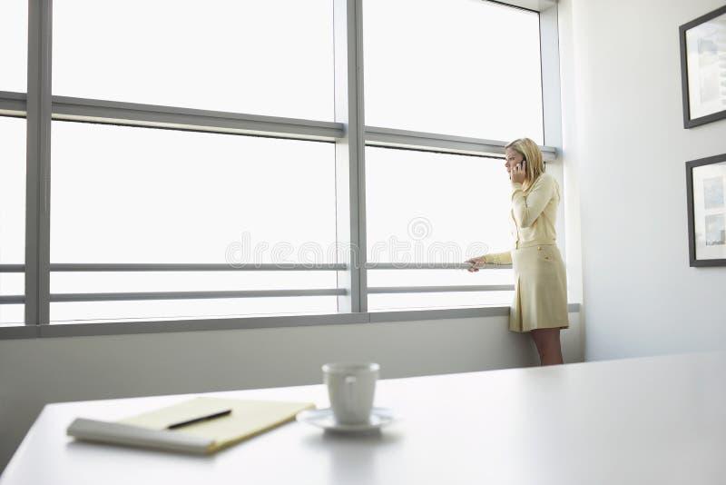 Επιχειρηματίας που χρησιμοποιεί το κινητό τηλέφωνο από το παράθυρο γραφείων στοκ εικόνες