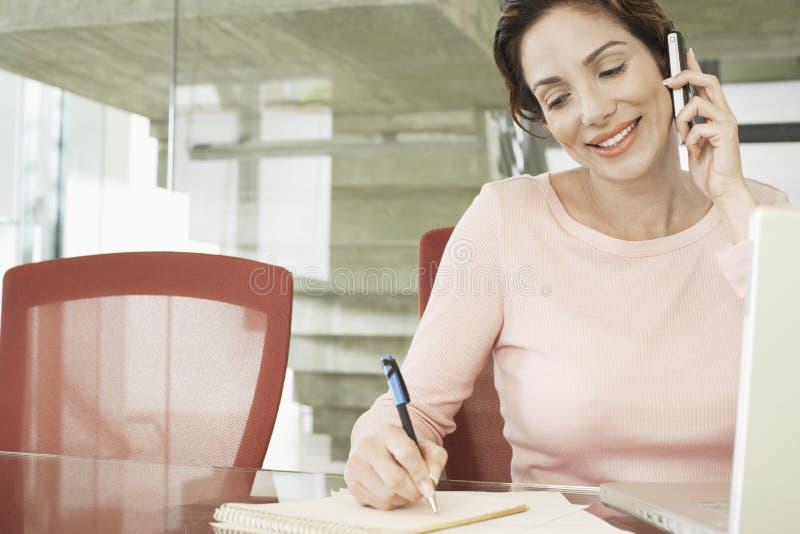 Επιχειρηματίας που χρησιμοποιεί το κινητό τηλέφωνο γράφοντας στο σημειωματάριο στοκ φωτογραφίες