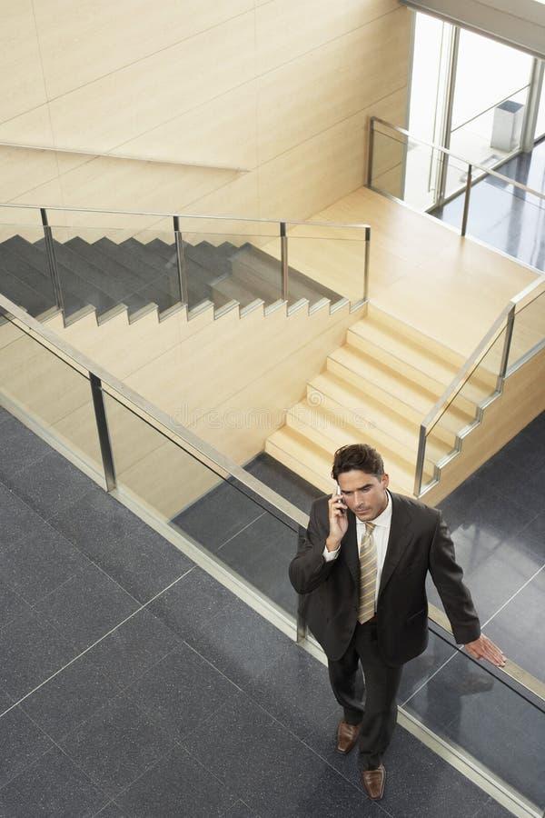 Επιχειρηματίας που χρησιμοποιεί το κινητό τηλέφωνο κλίνοντας στο κιγκλίδωμα γυαλιού στοκ εικόνα
