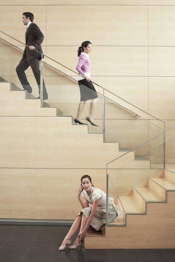 Επιχειρηματίας που χρησιμοποιεί το κινητό τηλέφωνο με τους συναδέλφους που αναρριχούνται στα σκαλοπάτια μέσα στοκ φωτογραφίες