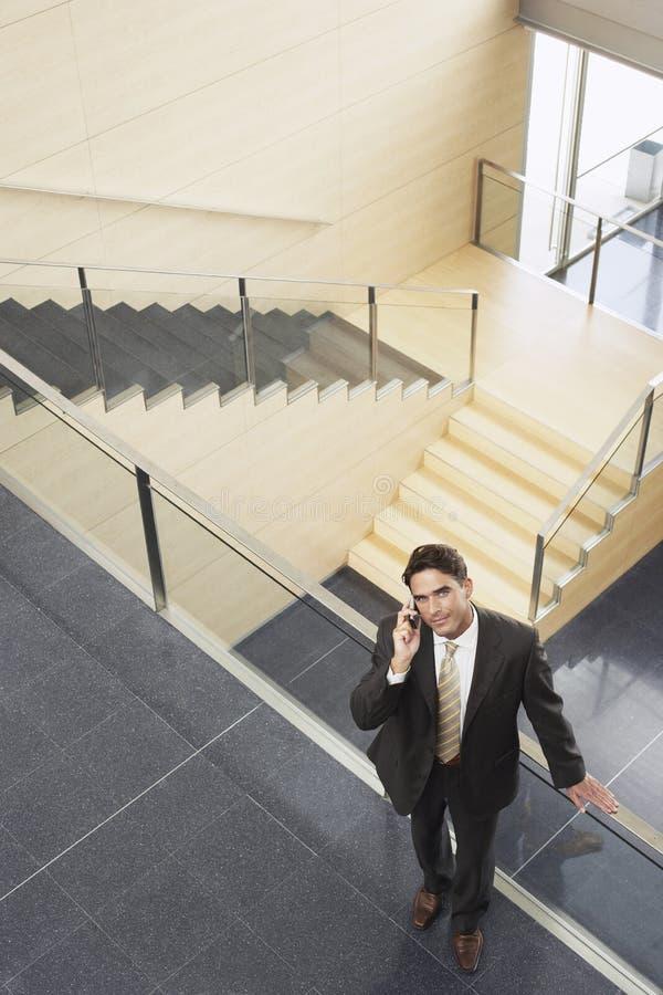 Επιχειρηματίας που χρησιμοποιεί το κινητό τηλέφωνο υπερασπιμένος το κιγκλίδωμα γυαλιού στοκ εικόνα
