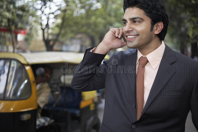 Επιχειρηματίας που χρησιμοποιεί το τηλέφωνο κυττάρων στην οδό πόλεων στοκ εικόνα με δικαίωμα ελεύθερης χρήσης