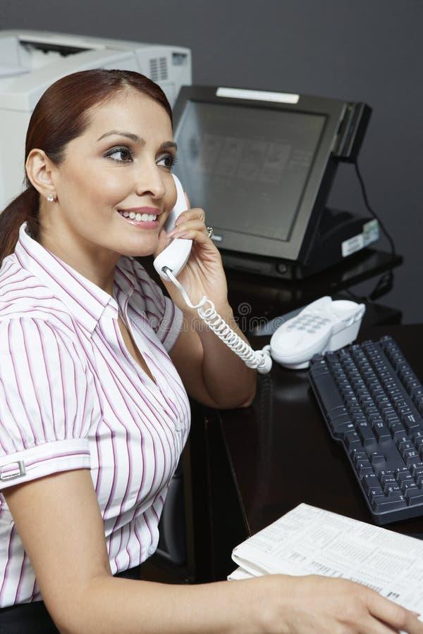 Επιχειρηματίας που χρησιμοποιεί το τηλέφωνο στην αρχή στοκ εικόνες