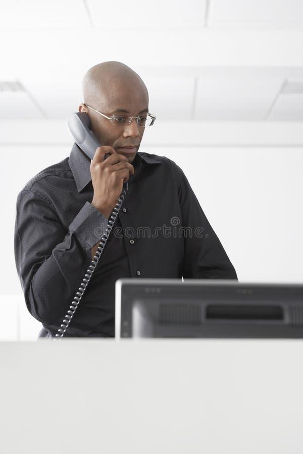 Επιχειρηματίας που χρησιμοποιεί το τηλέφωνο στο γραφείο υπολογιστών στοκ φωτογραφίες
