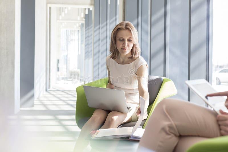 Επιχειρηματίας που χρησιμοποιεί το lap-top διαβάζοντας το αρχείο από το συνάδελφο στην αρχή στοκ φωτογραφίες με δικαίωμα ελεύθερης χρήσης