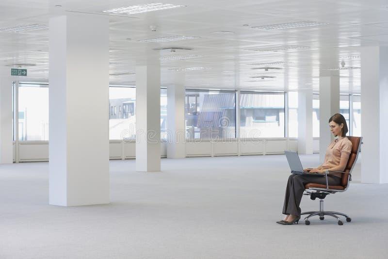 Επιχειρηματίας που χρησιμοποιεί το lap-top στην έδρα στο κενό γραφείο στοκ εικόνα