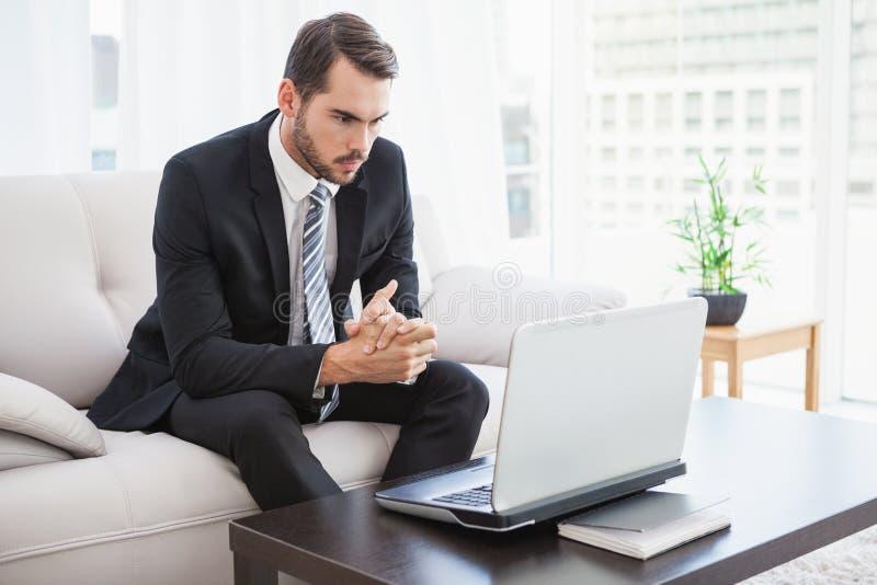 Επιχειρηματίας που χρησιμοποιεί το lap-top στον καναπέ του στοκ εικόνα με δικαίωμα ελεύθερης χρήσης