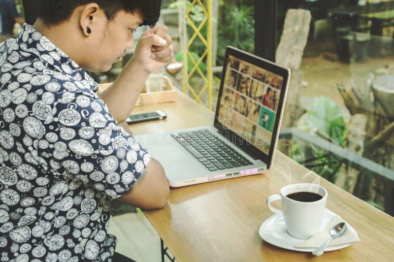 Επιχειρηματίας που χρησιμοποιεί το lap-top του στο κατάστημα Cofee στοκ εικόνες με δικαίωμα ελεύθερης χρήσης