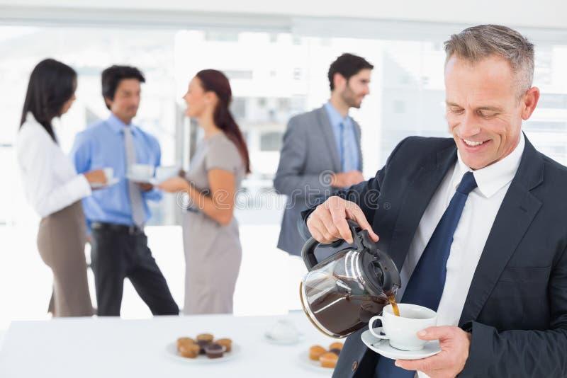 Επιχειρηματίας που χύνεται κάποιο καφέ στοκ φωτογραφία