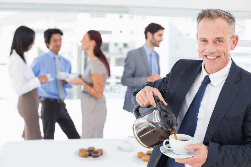 Επιχειρηματίας που χύνεται κάποιο καφέ στοκ εικόνες