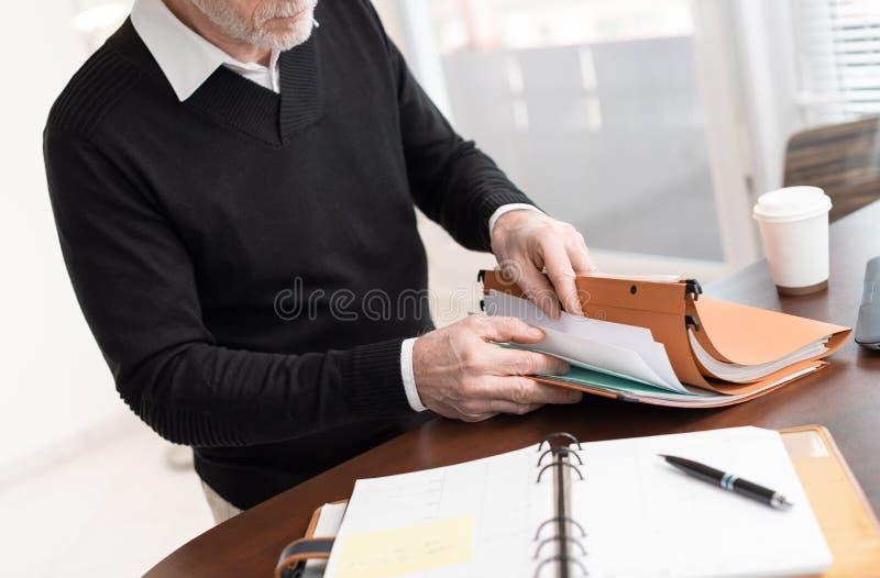 Επιχειρηματίας που ψάχνει το έγγραφο στο φάκελλο στοκ εικόνα