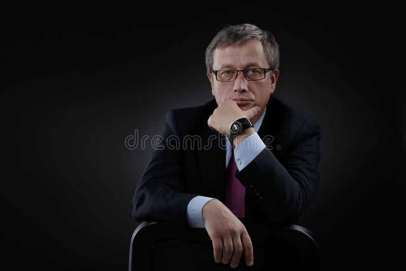 Επιχειρηματίας σε ένα κοστούμι σε ένα σκοτεινό υπόβαθρο στοκ εικόνα με δικαίωμα ελεύθερης χρήσης