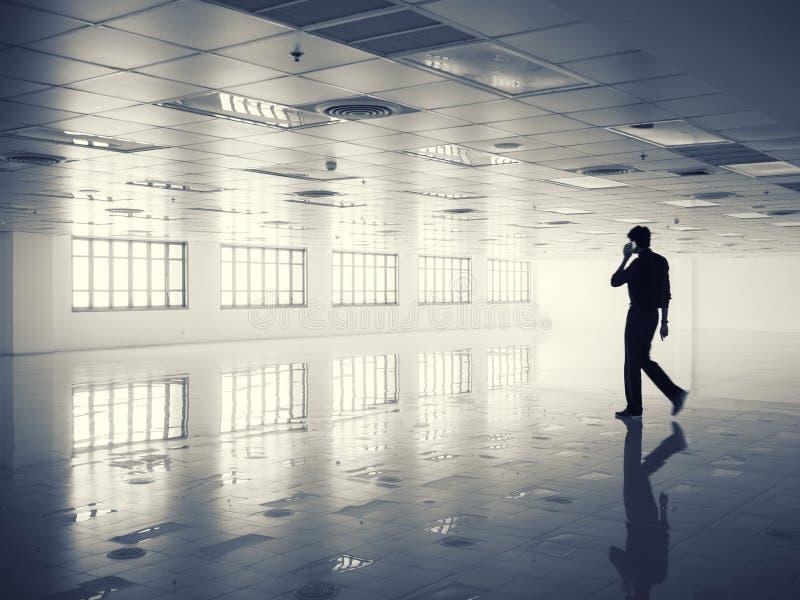 Επιχειρηματίας σκιαγραφιών που μιλά στο τηλέφωνο στο σύγχρονο χώρο γραφείου στοκ εικόνα με δικαίωμα ελεύθερης χρήσης