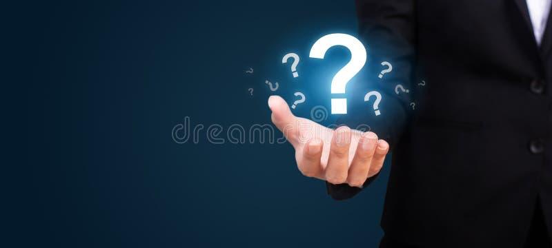 Επιχειρηματίας στα θολωμένα ερωτηματικά χεριών εκμετάλλευσης υποβάθρου στοκ φωτογραφία