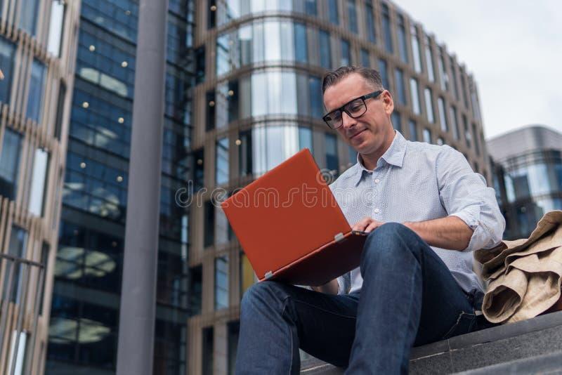 Επιχειρηματίας στα περιστασιακά ενδύματα που λειτουργούν στο lap-top στοκ φωτογραφίες