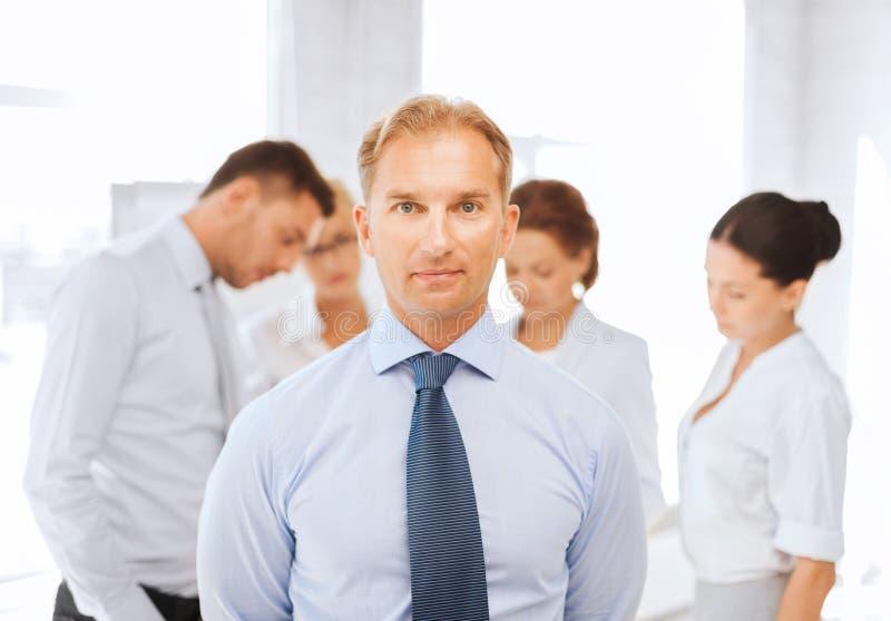 Επιχειρηματίας στην αρχή με την ομάδα σχετικά με την πλάτη στοκ εικόνα