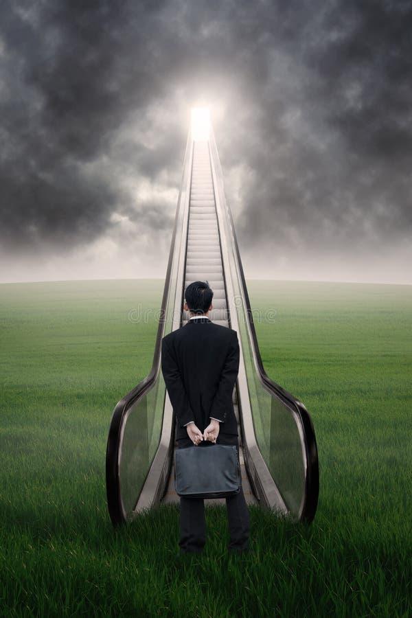 Επιχειρηματίας στην κυλιόμενη σκάλα κάτω από το cloudscape στοκ εικόνες