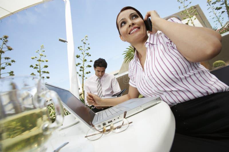 Επιχειρηματίας στην κλήση με το συνάδελφο στο υπόβαθρο στοκ εικόνες με δικαίωμα ελεύθερης χρήσης