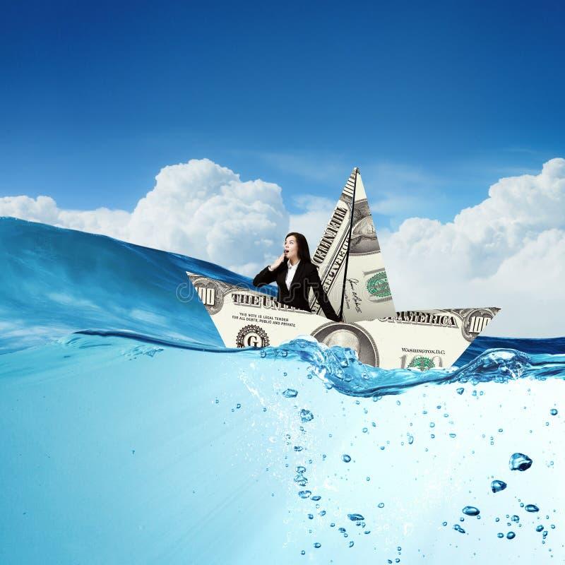 Επιχειρηματίας στη βάρκα φιαγμένη από τραπεζογραμμάτιο δολαρίων στοκ φωτογραφία με δικαίωμα ελεύθερης χρήσης