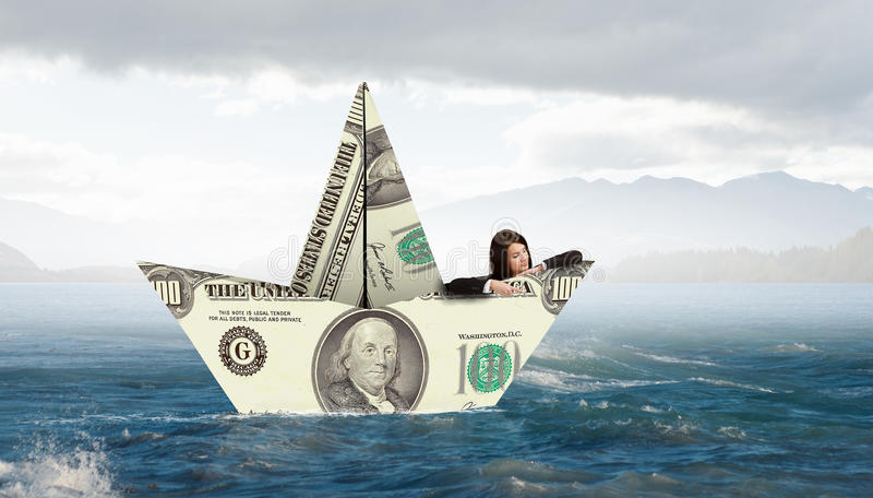 Επιχειρηματίας στη βάρκα φιαγμένη από τραπεζογραμμάτιο δολαρίων στοκ εικόνες