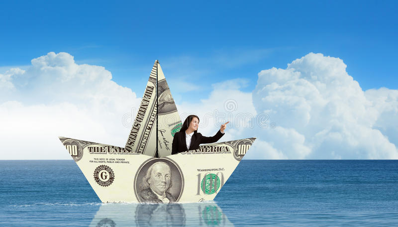 Επιχειρηματίας στη βάρκα φιαγμένη από τραπεζογραμμάτιο δολαρίων στοκ εικόνες με δικαίωμα ελεύθερης χρήσης
