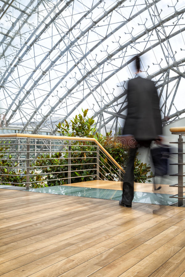 Επιχειρηματίας στη βιασύνη, θολωμένοι κίνηση άνθρωποι πέρα από το κτίριο γραφείων στοκ εικόνες