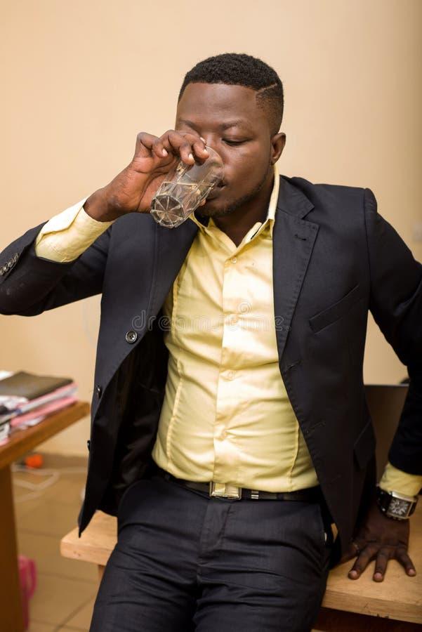 Επιχειρηματίας στο γραφείο και στο πόσιμο νερό στοκ εικόνες