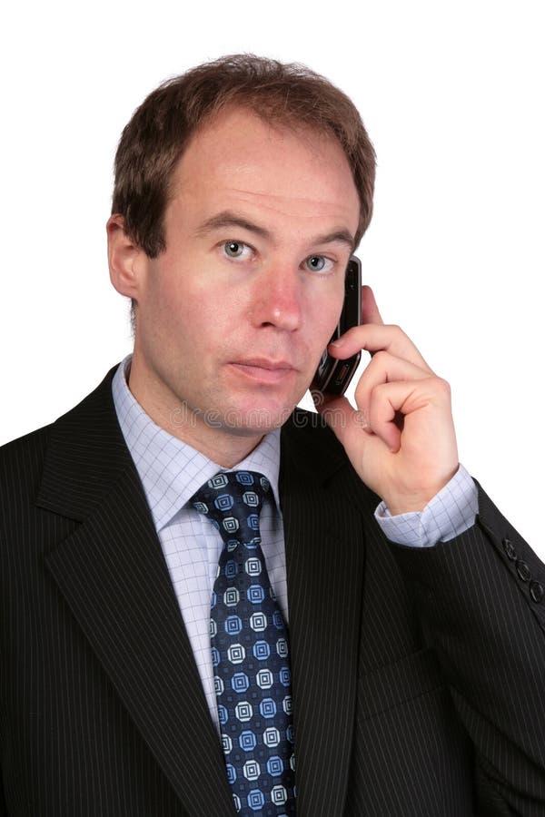 Επιχειρηματίας στο κινητό τηλέφωνο που κοιτάζει προς τη κάμερα στοκ εικόνες με δικαίωμα ελεύθερης χρήσης