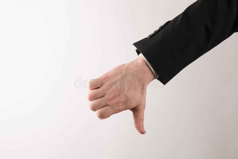 Επιχειρηματίας στο κοστούμι με τους αντίχειρες κάτω στοκ εικόνα