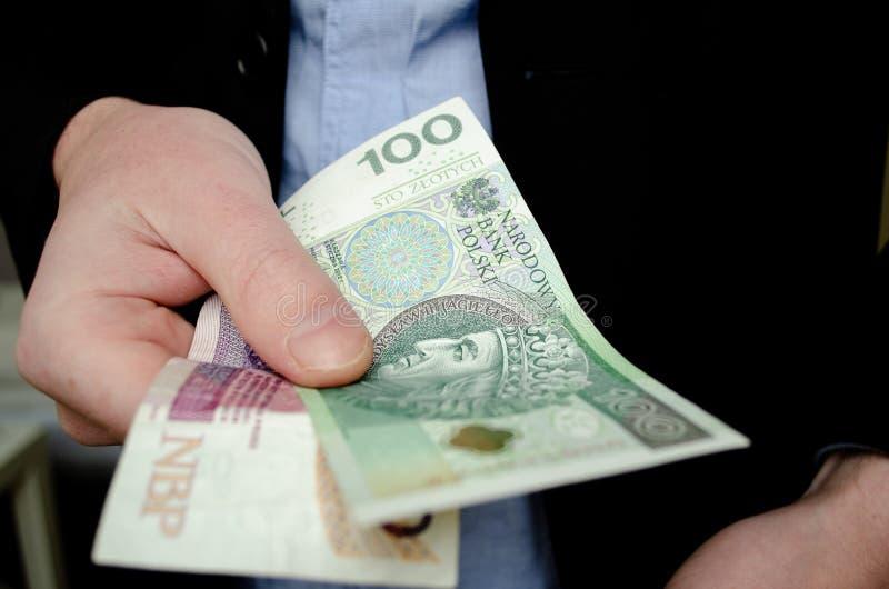 Επιχειρηματίας στο κοστούμι που δίνει τα χρήματα Εκατόν είκοσι πολωνικός zloty, κλείνει επάνω στοκ εικόνες