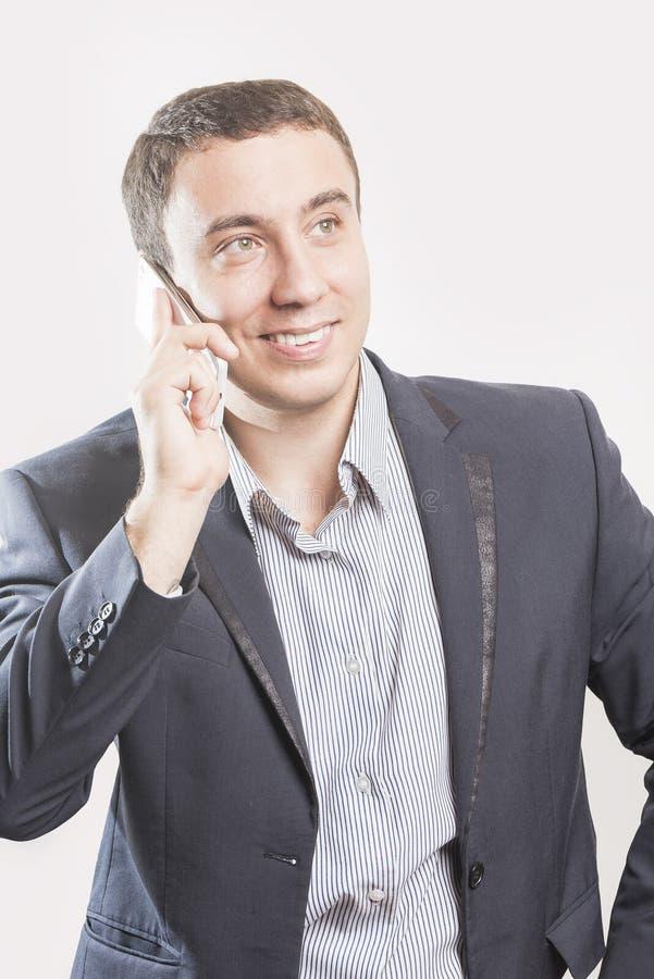 Επιχειρηματίας στο κοστούμι που μιλά στο τηλέφωνο και το χαμόγελο στοκ φωτογραφία με δικαίωμα ελεύθερης χρήσης