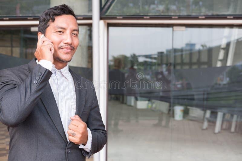 Επιχειρηματίας στο κοστούμι που μιλά στο έξυπνο τηλέφωνο στεμένος outsid στοκ εικόνα