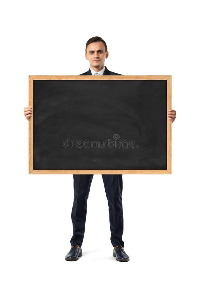 Επιχειρηματίας στο κοστούμι που στέκεται και που κρατά τον πίνακα στο ξύλινο πλαίσιο, που απομονώνεται στο άσπρο υπόβαθρο στοκ εικόνα με δικαίωμα ελεύθερης χρήσης