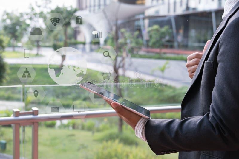 Επιχειρηματίας στο μαξιλάρι αφής εκμετάλλευσης κοστουμιών στεμένος έξω από το bui στοκ εικόνες