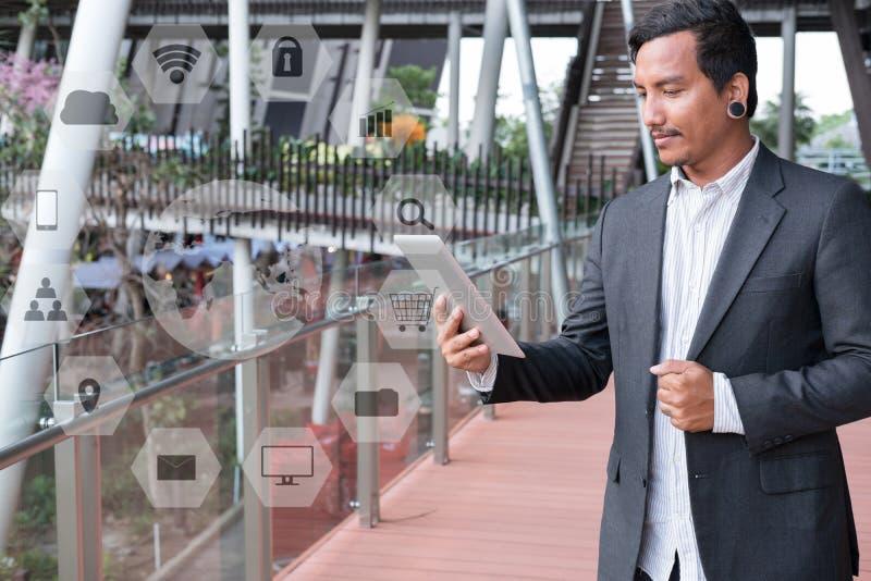 Επιχειρηματίας στο μαξιλάρι αφής εκμετάλλευσης κοστουμιών στεμένος έξω από το bui στοκ εικόνα