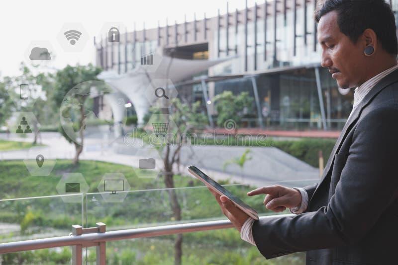 Επιχειρηματίας στο μαξιλάρι αφής εκμετάλλευσης κοστουμιών στεμένος έξω από το bui στοκ φωτογραφίες