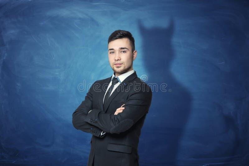 Επιχειρηματίας στο μπλε υπόβαθρο πινάκων κιμωλίας με τη σκιά του που έχει τα κέρατα διαβόλων στοκ εικόνα με δικαίωμα ελεύθερης χρήσης
